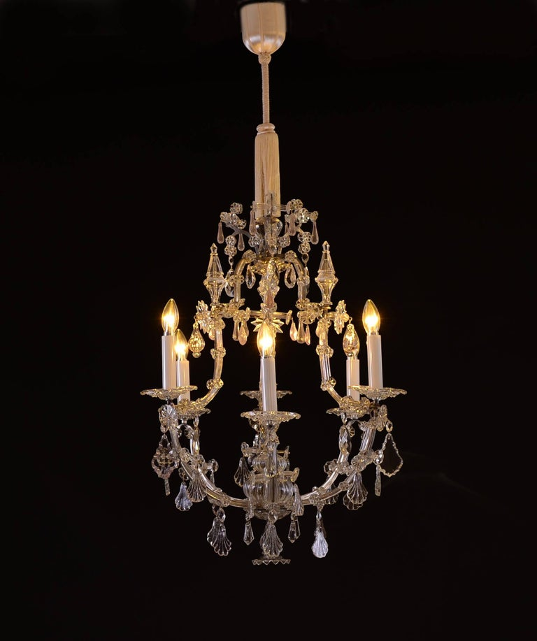 Saloon-Chandelier crown-shaped Baroque-style bronce, metal-frame partly covered with glass rich in hand-cut-glass-decoration dripping down dishes