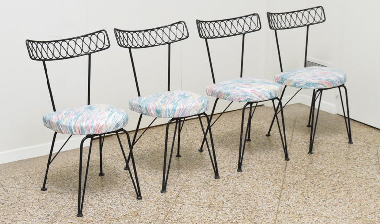 Set of four wrought iron ribbon chairs attributed to Maurizio Tempestini for Salterini. Please inquire about the following additional pieces we have for sale in the Tempestini/Salterini ribbon pattern: wall mirrors, armchairs, table, and headboards.