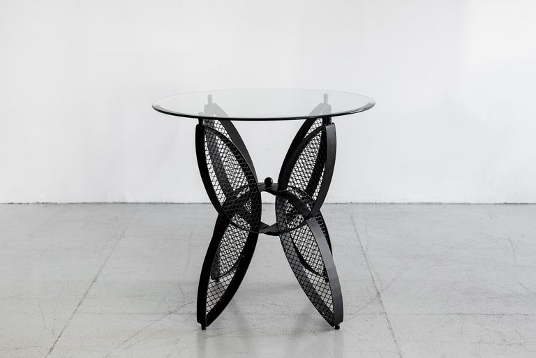 Fantastic sculptural pair of side tables attributed to Salterini in the shape of butterfly wings with signature perforated iron. New glass. Measures: Base W 20