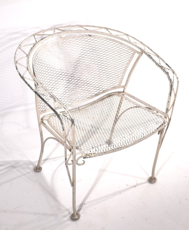 Nice Salterini garden, patio, poolside chair having a wrought iron frame with zig zag metalwork pattern, and metal mesh seat and back. The chair is in very good, original condition, free of breaks, bends, damage or repairs. The paint finish shows