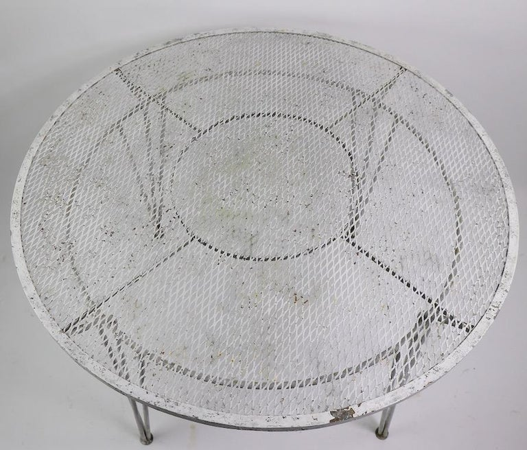 Classic Salterini midcentury garden table with wrought iron frame and metal mesh top. Great Modernist design, very good original condition, paint finish shows wear, normal and consistent with age. Use as is or we offer professional powder coating if