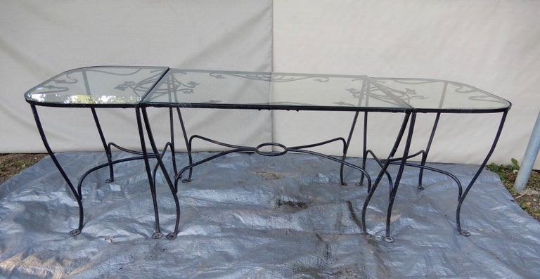 This is a Salterini wrought iron nine piece dining set in the desirable Mt Vernon pattern. It is comprised of three tables, a dining table that is 32 x 48, and a pair of console tables. The console tables can be used without the dining table in a