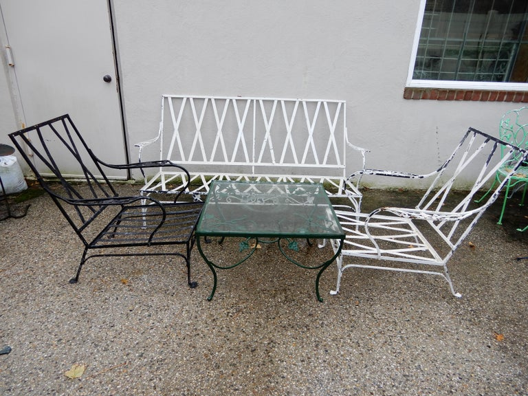 A vintage wrought iron patio set by premier manufacturer John Salterini. The patio set consists of 1 sofa, 2 club chairs and 1 matching coffee table all are wrought iron.