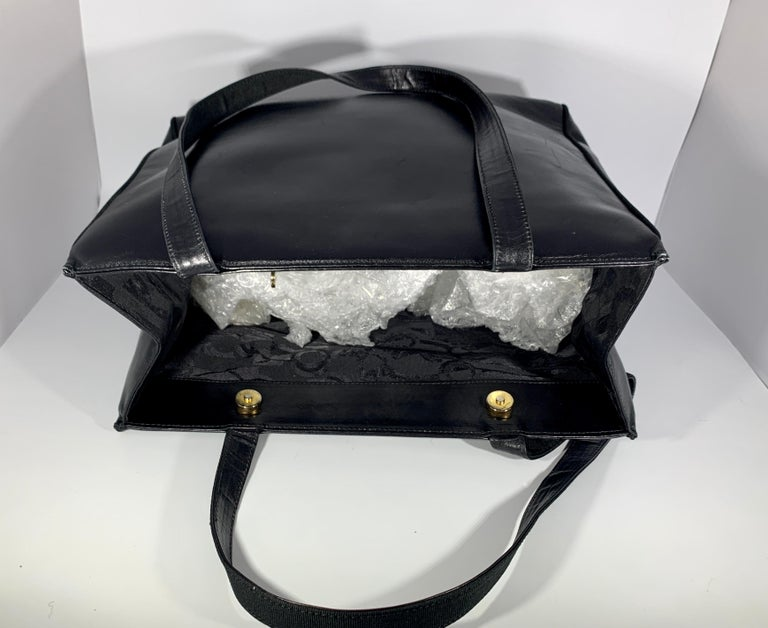Ferragamo Black smooth leather tote with  Two snap  button closure on the top. Opens in to a very spacious  and a large zippered pocket. i  Perfect for your laptop, books, and travel.  Made in Italy AQ 212530                 SIZE 13