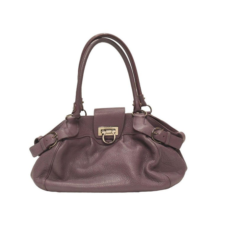 Gorgeous Salvatore Ferragamo Marisa shoulder bag in gorgeous violet leather with dual rolled shoulder straps and Gancio flip lock closure in silver toned hardware.  This beautiful bag features a SALVATORE monogram printed interior lining with inner