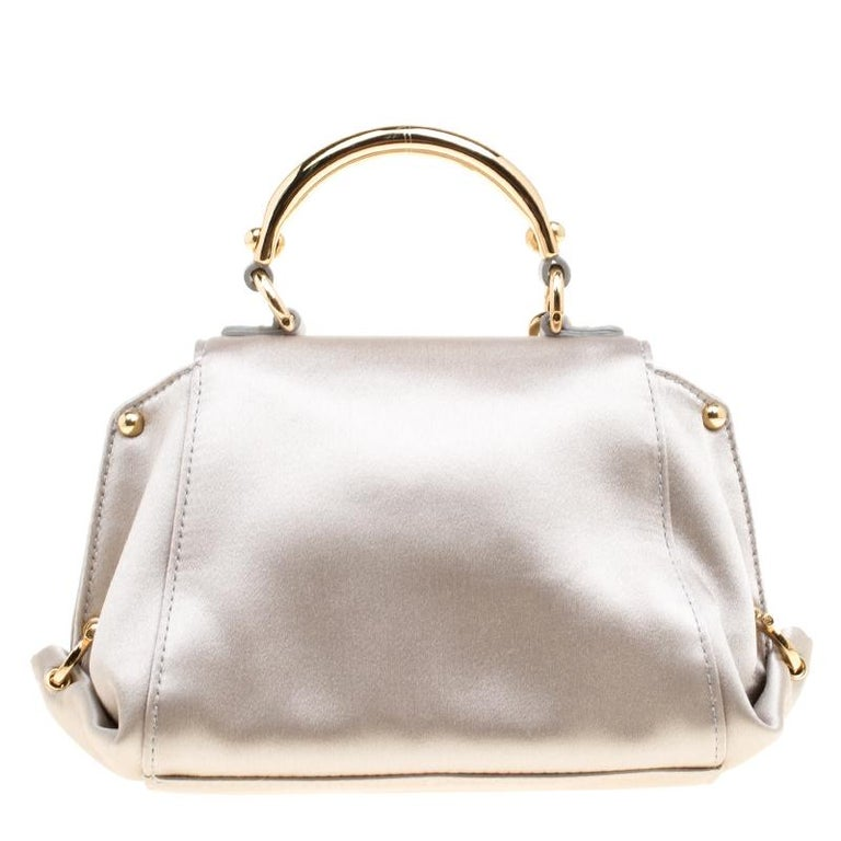 Carry this gorgeous Salvatore Ferragamo creation wherever you go and make people drool. Meticulously crafted from metallic grey satin, this bag has been styled with a top handle, a removable shoulder strap and a leather interior to hold your