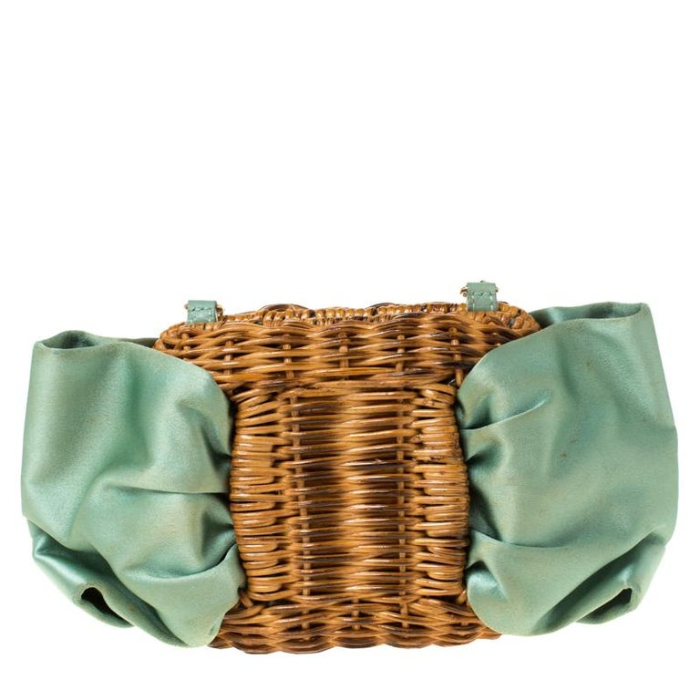 Made in Italy, and blooming with beauty is this beautiful chain clutch by Salvatore Ferragamo. It is made from woven rattan and styled with mint green satin in a bow design. It also features a gold-tone chain and a top lock that opens to a satin