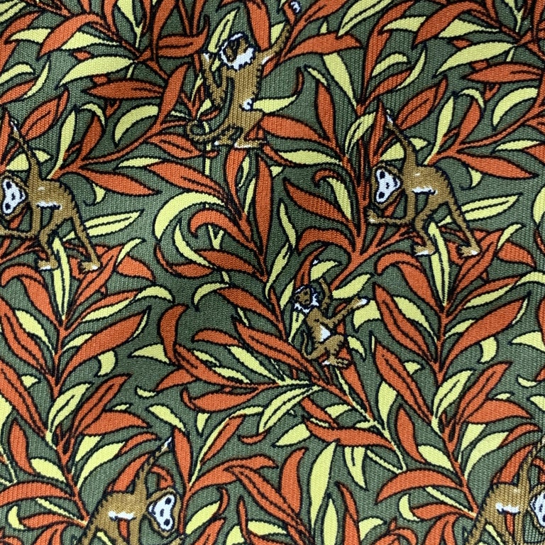 SALVATORE FERRAGAMO necktie comes in olive green and burnt orange pattern silk twill with all over monkeys print. Made in Italy.  Very Good Pre-Owned Condition.  Width: 3.5 in.