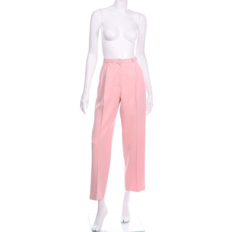 These vintage Salvatore Ferragamo pink wool trousers have sleek pleated straight leg and would fit in to any modern wardrobe. The pants have a waistband with small belt loops and  two front pleats with a pressed center pleat down the leg to the hem.
