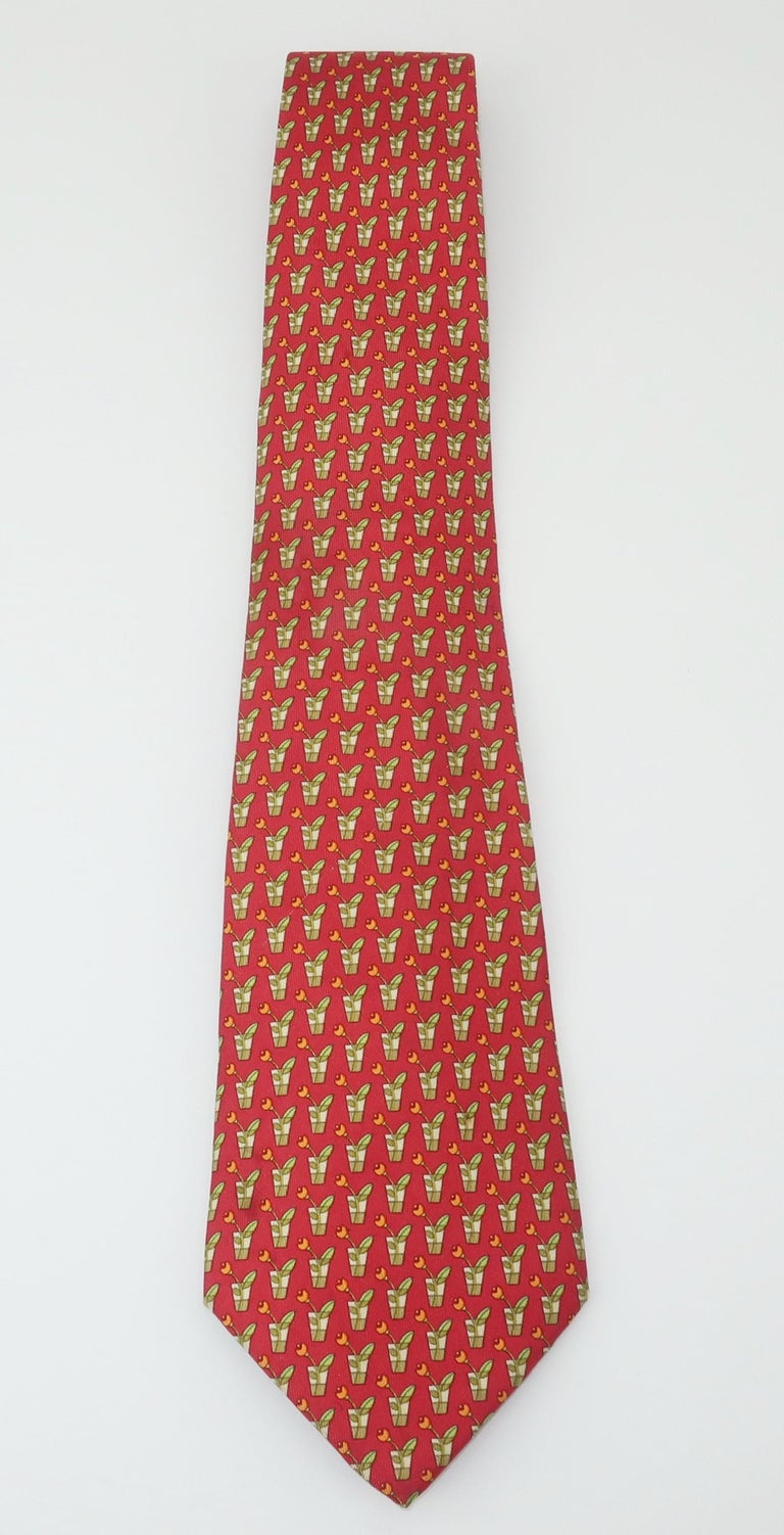 Ferragamo creates a menswear silk necktie with a cut flower motif in shades of watermelon red, sage green and light orange.  Beautifully made with the quality one would expect from Ferragamo.  Good to fair previously owned condition with a shadowy