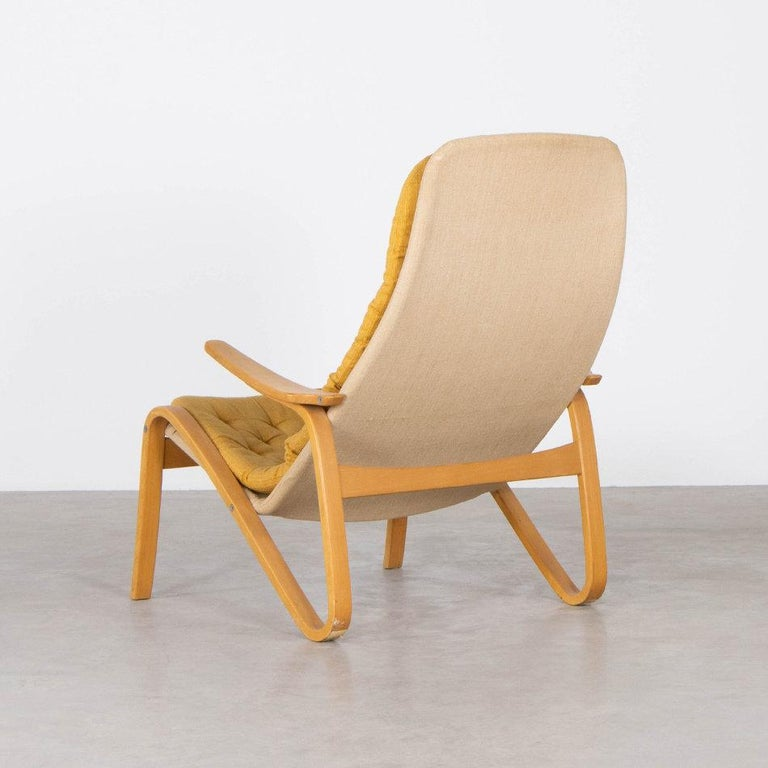 Nice lounge chair (Metro) designed by Sam Larsson for DUX Sweden. Birch plywood frame with canvas cover and cushions with ochre fabric. All in good original condition.