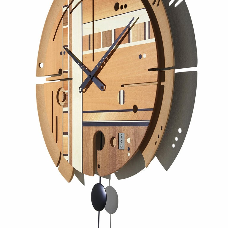 A functional work of art, this clock boasts a handmade face with a structure in wood pulp and a surface enriched with inlays of beechwood, maple, wenge, Canaletto walnut, and Italian walnut with a natural matte finish. Easy to read, this wall clock