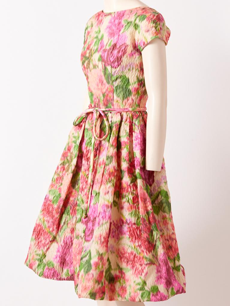 Samuel Winston, crinkled silk, impressionistic, soft tones, floral pattern, dress having a bateau neckline, cap sleeve, fitted bodice, and full gathered skirt. Tubular self belt ties at the waist. C. 1960's.