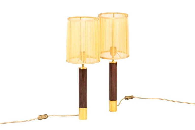 """Santa & Cole, attributed to. Pair of tubular shape """"Basica"""" lamps in rosewood, surrounded by gilt brass ring on the bottom.  Work realized in the 1980s.  New and functional electrical system.  The price doesn't include the lampshade price."""