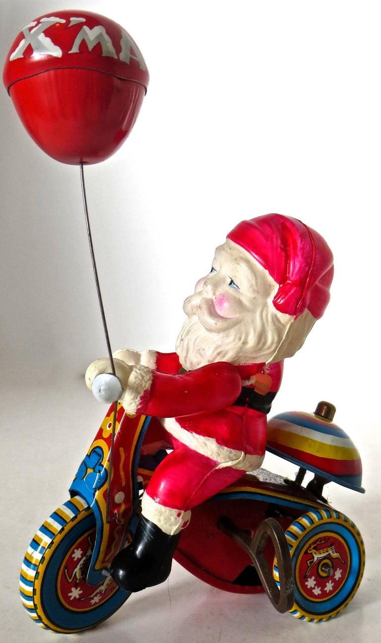 The celluloid Santa and tin tricycle indicate a mid-1950s manufacture for this charming Japanese wind up toy which comes with the original box in which it was shipped. Unlike most examples found of this toy, this example is near mint and operates