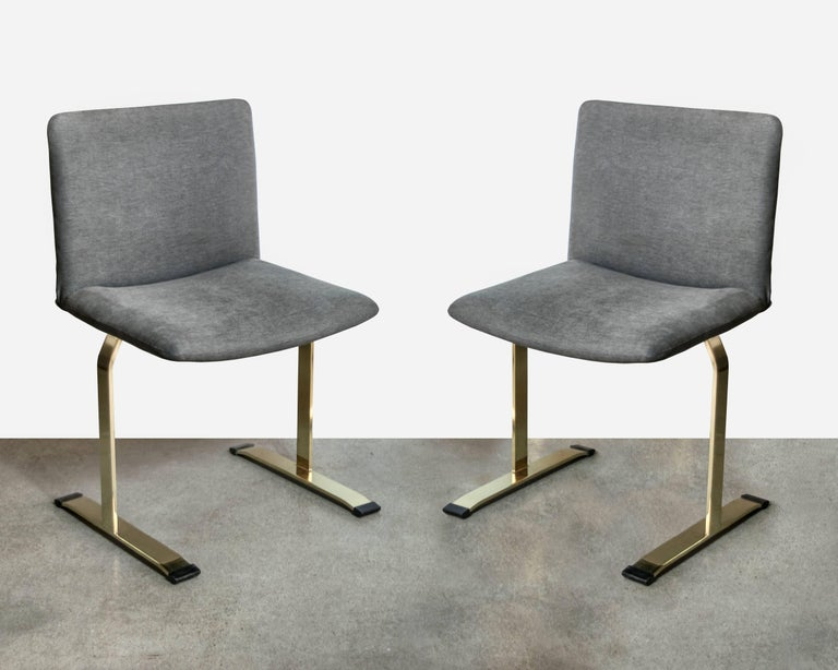 Rare set of brass finished Saporiti dining chairs with the original black rubber stoppers. Brass work has no scratches, scuffs or pitting. They are upholstered in a mushroom colored knit with no stains, tears or fading. Unusual to find a set with
