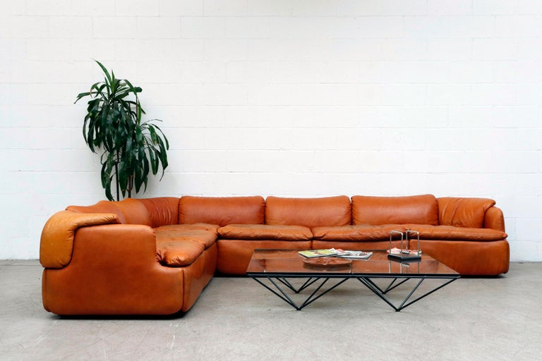 Incredible midcentury Alberto Rosselli 'Confidential' sofa for Saporiti, Italia. Burnt orange leather sectional with puzzle piece cushions. Color touch-up to seat cushion tops, in otherwise original condition with visible wear and patina.