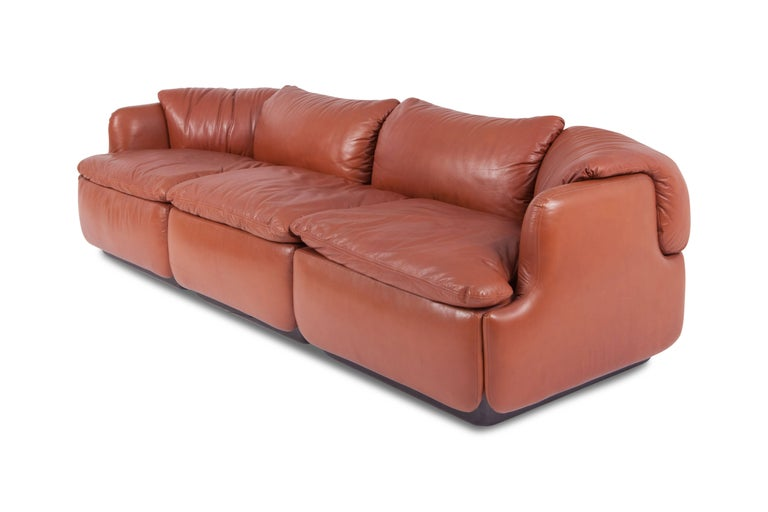 Iconic whiskey colored sofa in high quality leather, designed by Italian architect Alberto Rosselli in 1972 for Saporiti Italia. It is one of the first modular sofas ever produced for private homes. The elements are connected by the puzzle like