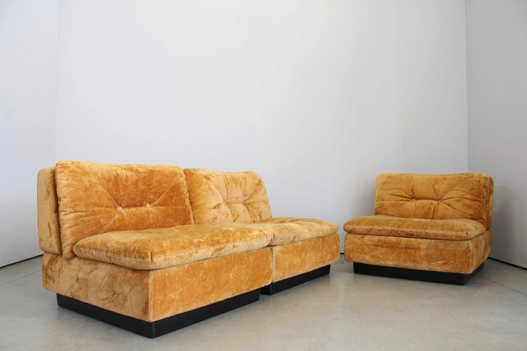 Design from the 1970s. This sofa from Saporiti Italia has a orange/ yellow soft velour fabric. The sofa consist 3 modules that can arrange to a 3-seat sofa or as a 2-seat sofa and a chair. Good condition.  Dimensions: Module Width 83 cm Depth 85