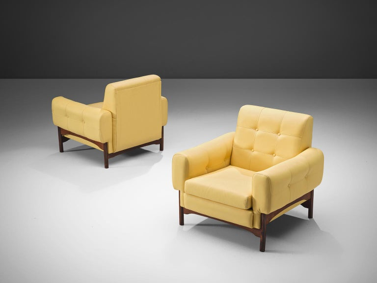Saporiti, pair of lounge chairs yellow faux leather upholstery, rosewood, Italy, 1960s.  This elegant, geometric pair of lounge chairs feature a mellow soft yellow faux leather upholstery. The chairs stand on four little tapered wooden legs that