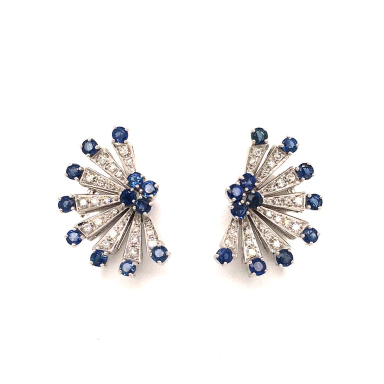 These semi-star shaped earclips in 18 karat white gold are set with 24 round cut sapphires, total weight approximately 2.88 carats, and 48 single cut diamonds of G/H color and vs clarity, total weight approximately 0.96 carats.  Dimensions approx.: