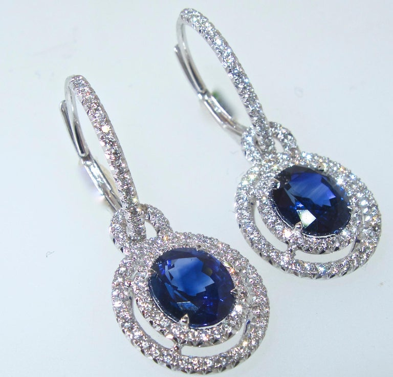 Sapphire and diamond earrings.  The natural vivid blue oval sapphires, are very fine quality, finely matched, with cutting as evident of their proportions, and the brightness of the stones.  The sapphires weigh 3.89 totally.  They are accented by