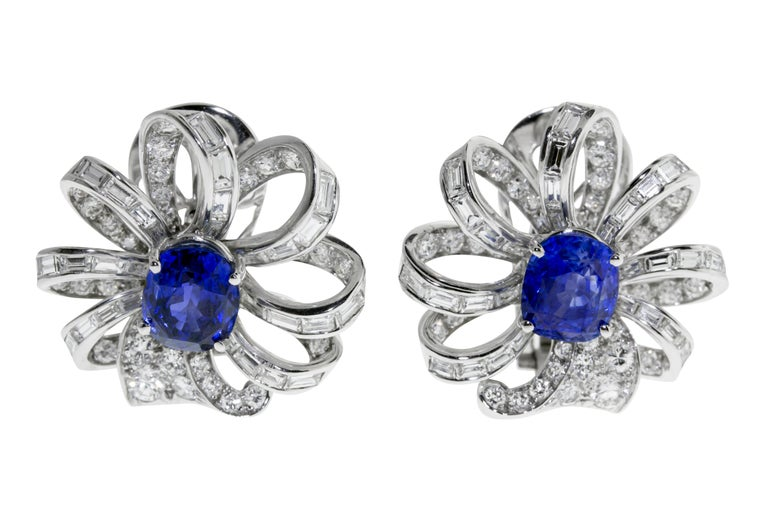 These earrings feature 10.37 grams of platinum delicately looped to mimic a flower circling two vibrant blue sapphires. 78 round diamonds, weighing a total of approximately 3.00 - 3.50 carats, F-G color, VVS-VS. 56 baguette-cut diamonds, weighing a