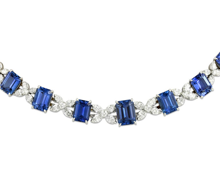 This breathtaking necklace by legendary jewelry designer Oscar Heyman features 26 emerald cut sapphires totaling 85.21 carats. Dotted between the blue gemstones are both marquise and round cut white diamonds in a striking criss-cross pattern and