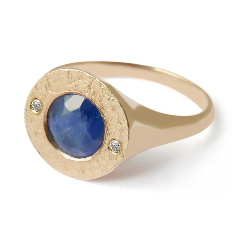 This textured signet ring features a natural Sri Lankan sapphire and two white diamond accents set in a shimmering texture crafted in solid 14-carat gold.  The ring is finished with a high polish on the sides and band for a comfortable fit.  This