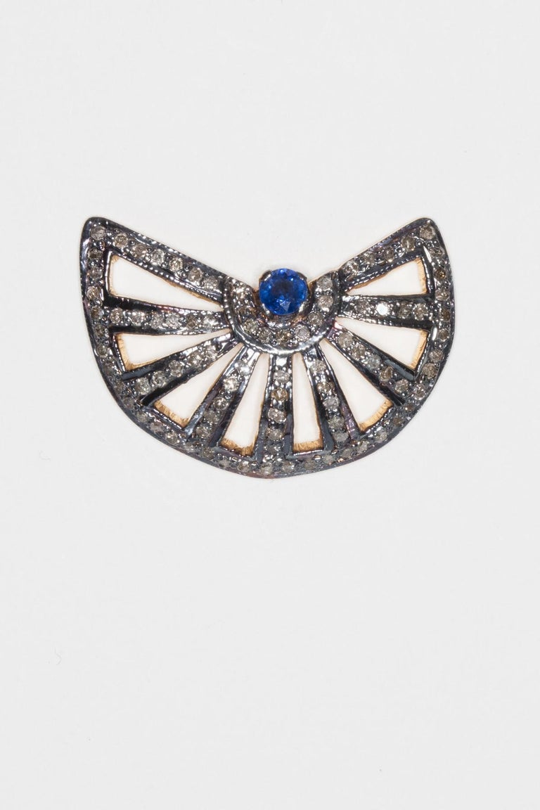 Faceted blue sapphire at center of fan-shaped stud earrings with pave`-set diamonds.  Set in oxidized sterling silver with 18K gold post for pierced ears.  Sapphires are .87 carats, diamonds are 1.71 carats.