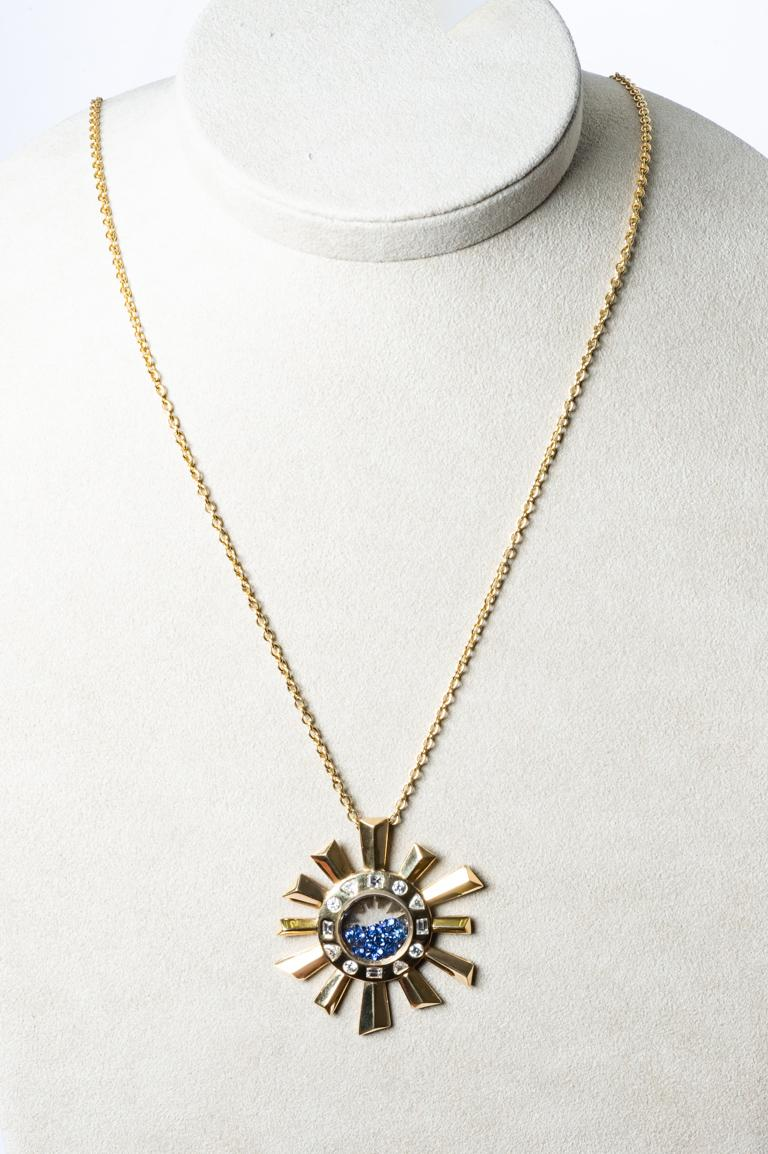 Zénith Necklace long chain surmounted by a yellow gold pendant in sun shape. The pendant is free on the chain. Diamonds of different sizes round, priangle and princess (square) weigh 1.31 carats in G/vs color. Inside the sapphires that can move and
