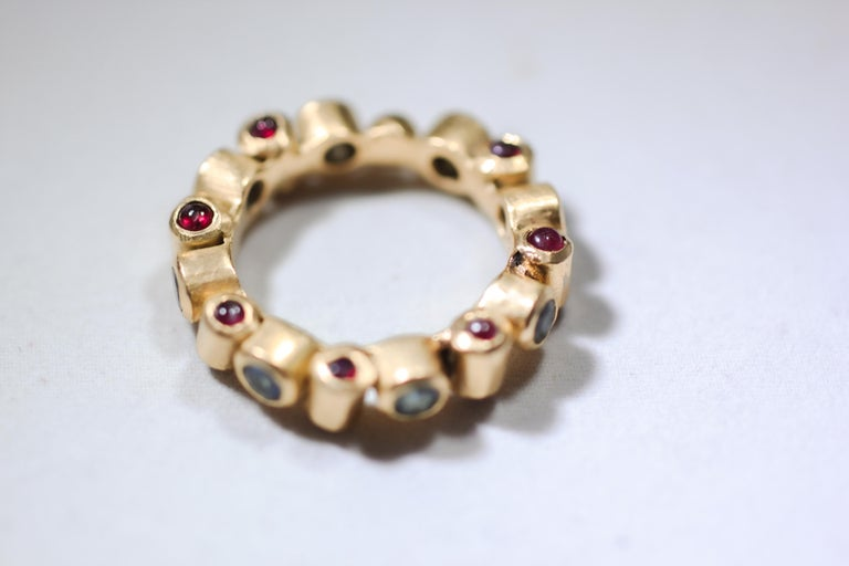 Cylinder Ring. An unusual 18K gold bezel bridal band ring is set on all three sides. On one side it displays untreated blue sapphires, brilliant-cut stones. Ruby cabochons are set on the top and the bottom. Like a sculpture, it appears slightly