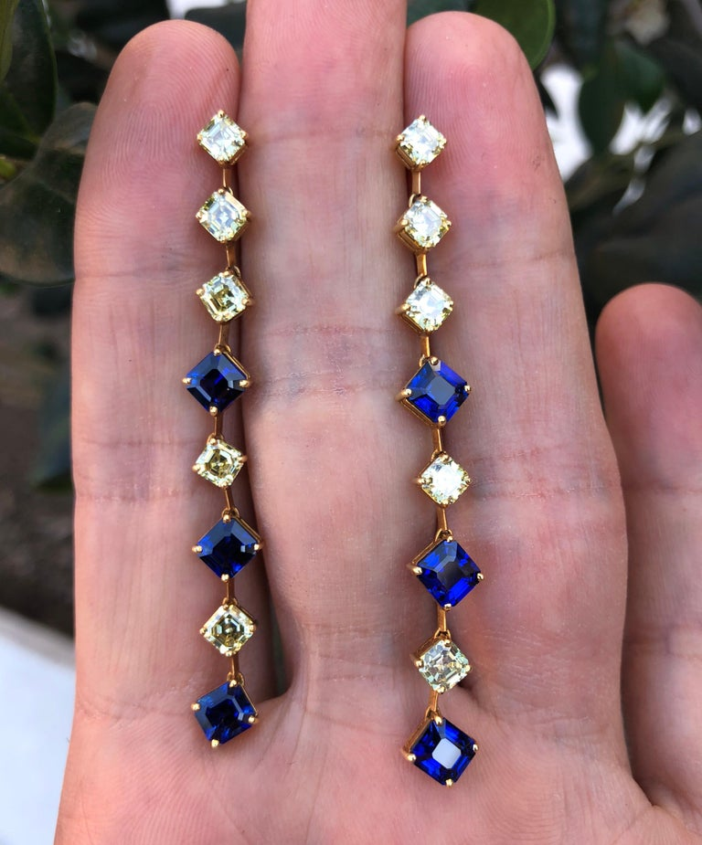 5.14 carats of royal blue, square emerald-cut sapphires, and 3.38 carats of fancy yellow Asscher cut diamonds, are hand set in these very unique 18K yellow gold drop earrings. Length: 2.5 inches. Crafted by extremely skilled hands in the