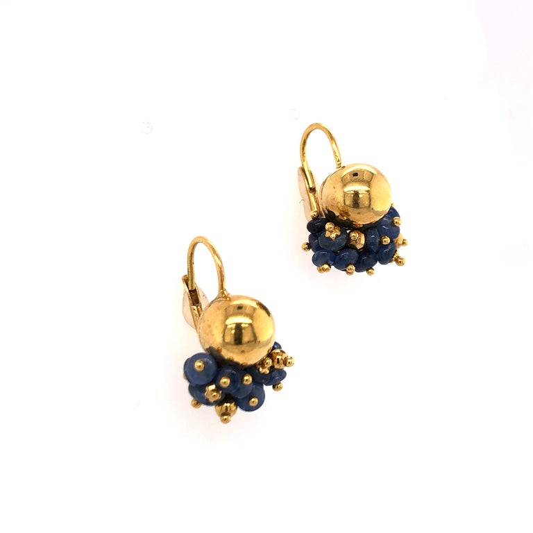 An fun bunch of Sapphire beads nestled under a 14K yellow gold ball make these earrings an unexpected addition to casual or dressy attire. So, get your favorite pair of jeans ready for these earrings!  Stamped: ME, (Star) 588, VI