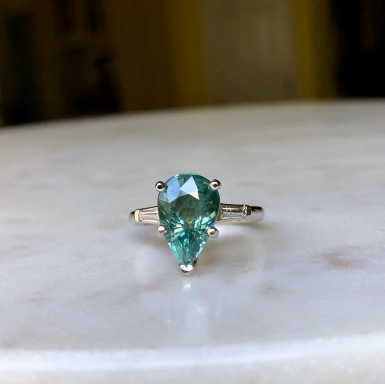 Simple elegant white gold setting with two tapered baguette cut diamonds, centering a big 5.28 carat Natural Blue Green Sapphire,