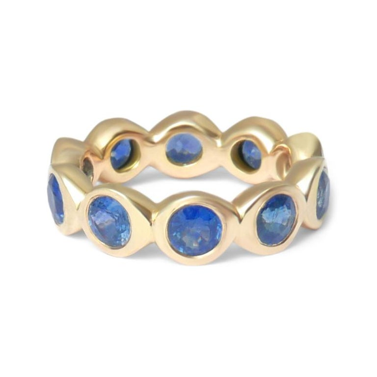 Crafted in solid 14-karat yellow gold, this substantial eternity band features ten round brilliant cut blue sapphires.  This ring is a UK size L 1/2 (equivalent to US size 5 7/8).  The total carat weight of the ten 4mm natural Sri Lankan blue
