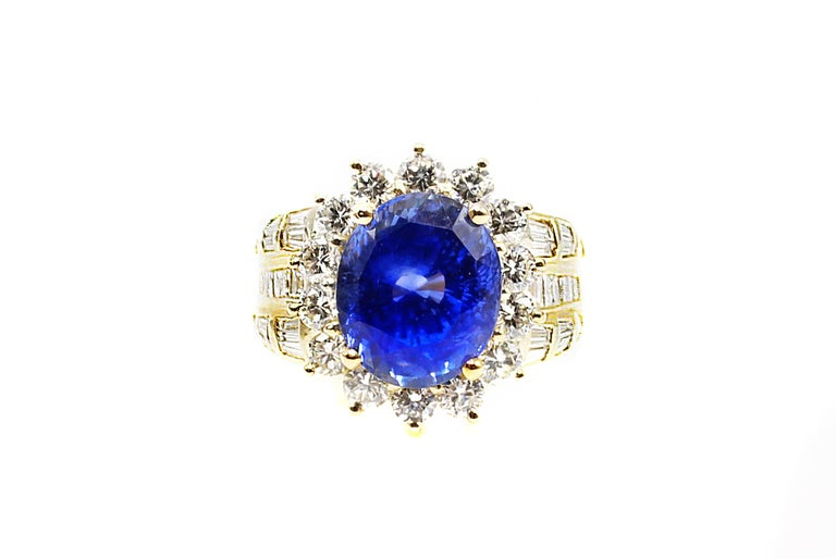 This beautiful sapphire is surrounded by 14 round cut diamonds and flanked by 3 rows on each side of 20 total baguette diamonds. Wonderfully handcrafted in platinum the diamond weight totals approximately 2 carats. The amazingly well cut oval