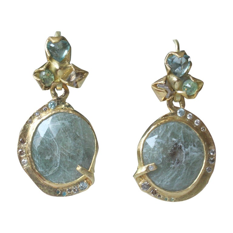 Lagoon dangle drop earrings. Brown diamonds, zircons, demantoid garnets are set in 21k gold creative bezels, 18k gold ear wires. Hanging blue-green sapphires are set in bezels and are surrounded by brown, blue, and white diamonds. One-of-a-kind,