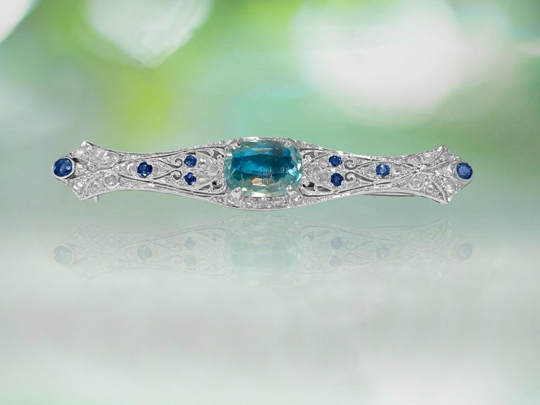 Metal: 18k white gold.   Diamonds: 0.90 cwt. SI clarity and G color. Rose cut diamonds.  Sapphire: 0.25 cwt (approx). Color: blue.  Aquamarine: 11.87 x 9.06mm stone. 4.50 carat aquamarine set in prongs. Oval cut aquamarine.   All stones are 100%
