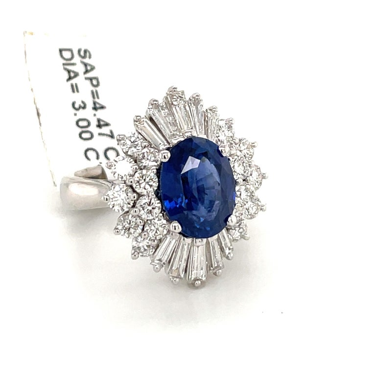 Impressive cluster earrings featuring a gorgeous oval shape blue Sapphires weighing 4.47 carats flanked with a cluster of round brilliants and tapered baguettes weighing 3 carats. Color G-H Clarity VS-SI  Gorgeous Sapphire color. Ring Is Sizeable.