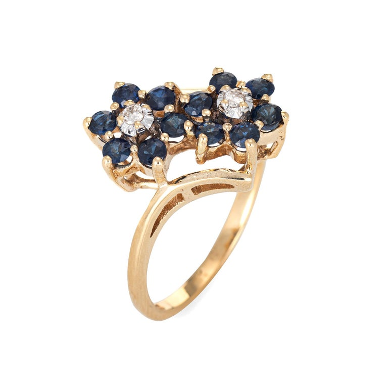 Finely detailed vintage sapphire & diamond double flower ring crafted in 10k yellow gold.   Two estimated 0.03 carat (each) round brilliant cut diamonds total an estimated 0.06 carats (estimated at I-J color and I1 clarity). 12 sapphires are