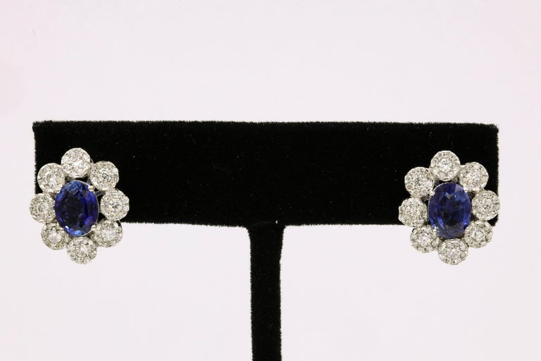 14K White gold earrings featuring two blue sapphires, 2.76 carats flanked with 144 round brilliants weighing 1.50 carats. Color G-H Clarity SI