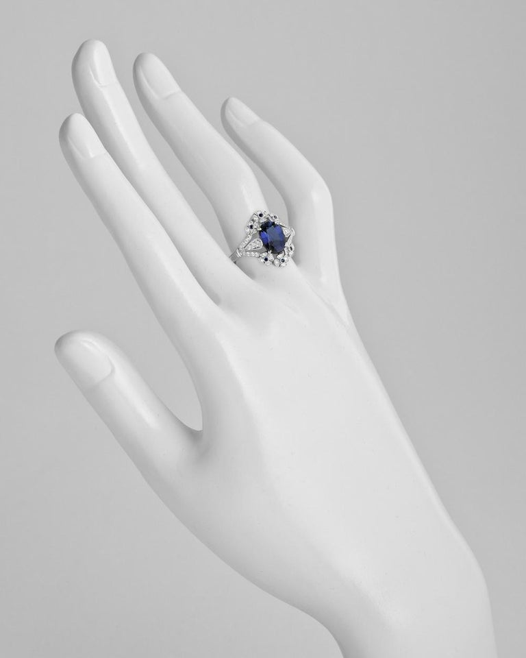 Sapphire and diamond ring, centering an oval-shaped sapphire weighing 2.04 carats with a floral patterned border accented by round-cut diamonds and sapphires, in platinum. Diamonds weighing 0.26 total carats and sapphire accents weighing 0.08 total