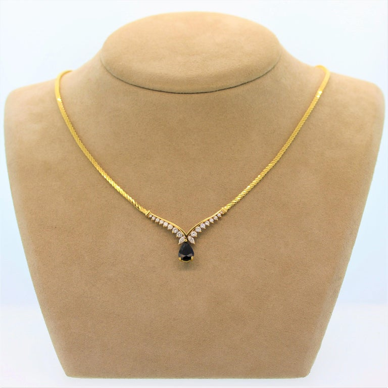 This timelessly elegant necklace features a blue sapphire of approximately 1.50 carats. The pear shape sapphire drops from a 14K yellow gold setting with 1.04 carats of marquise and round cut diamonds in a graduating pattern. The chain is a twist
