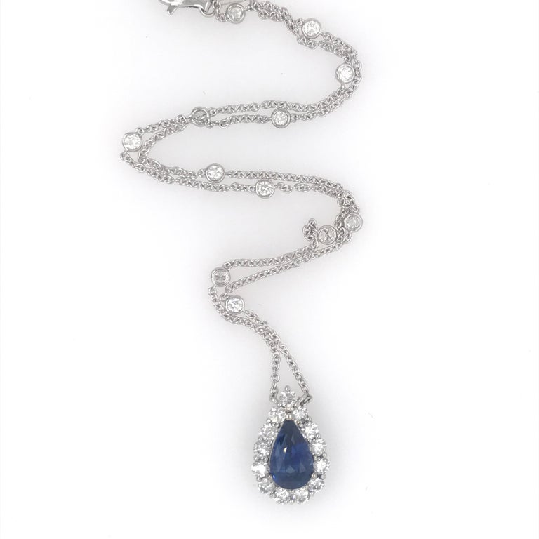 18K White gold necklace featuring one blue pear shape sapphire weighing 4.07 carats flanked with 13 round brilliants weighing 1.35 carats on a diamond by the yard weighing 0.69 carats. Color G-H