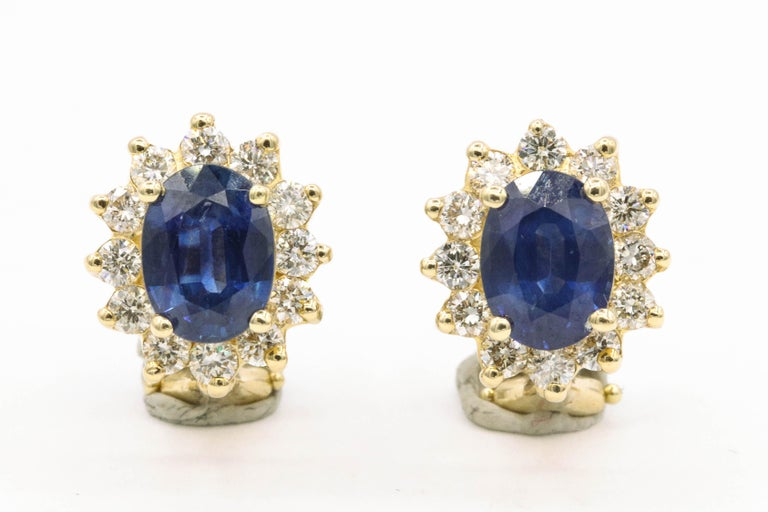 14K Yellow gold stud earrings featuring two oval shape blue sapphires, 3.20 carats flanked with round brilliants weighing 0.94 carats. Color G-H Clarity SI