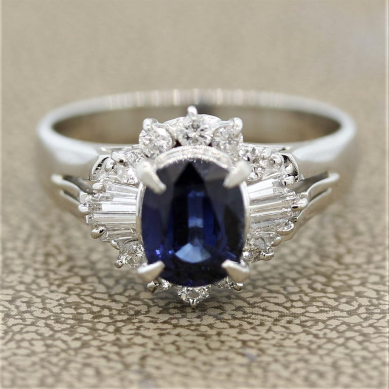 A lovely ring featuring a 2.07 carat oval shaped sapphire. It has a sweet and lively blue color which is free from any visible inclusions. It is surrounded by 0.61 carats of baguette and round brilliant cut diamonds set around the sapphire in a