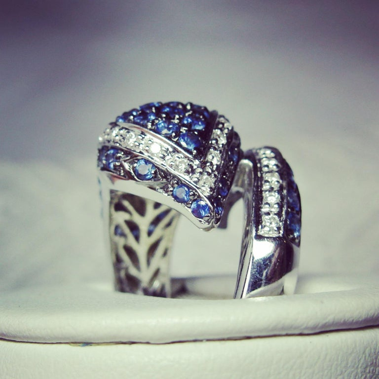 AN EXQUISITE AND DRAMATIC SNAKE RING SET WITH 57 GORGEOUS FINE BLUE NATURAL MINED SAPPHIRES TOTALING APPROXIMATELY 1.5 CARATS, AND 35 SPARKLING WHITE DIAMONDS, IN 18 KARAT WHITE GOLD - ALL THE RAGE! The ring depicts a spectacular snake.  The ring is