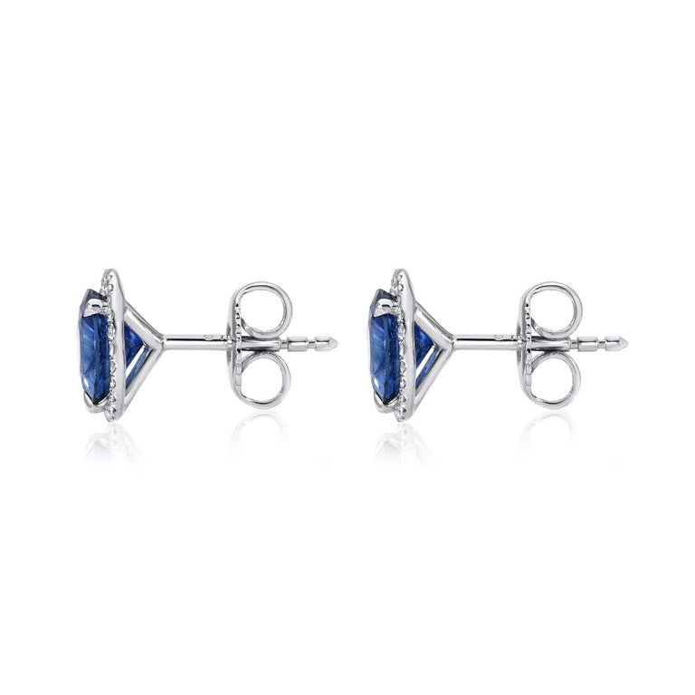 Sapphire stud earrings featuring a pair of round Sapphires weighing a total of 2.19 carats surrounded by a total of 0.25 carats of round brilliant diamonds, in 18K white gold. Returns are accepted and paid by us within 7 days of delivery.  Sapphire