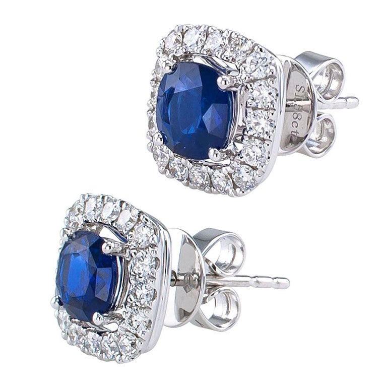 Sapphire and diamond white gold stud earrings. Showcasing a pair of cushion-shaped blue sapphires weighing approximately 1.58 carats, within a conforming border of round brilliant-cut diamonds all together totaling approximately 0.53 carat,